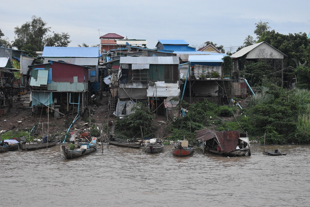 Mekong River village up close. Notice the amount of trash on the banks of the river.