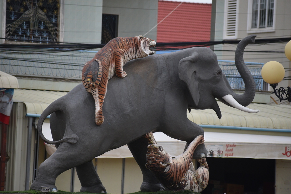 A really creative roundabout showing an elephant fighting two tigers.