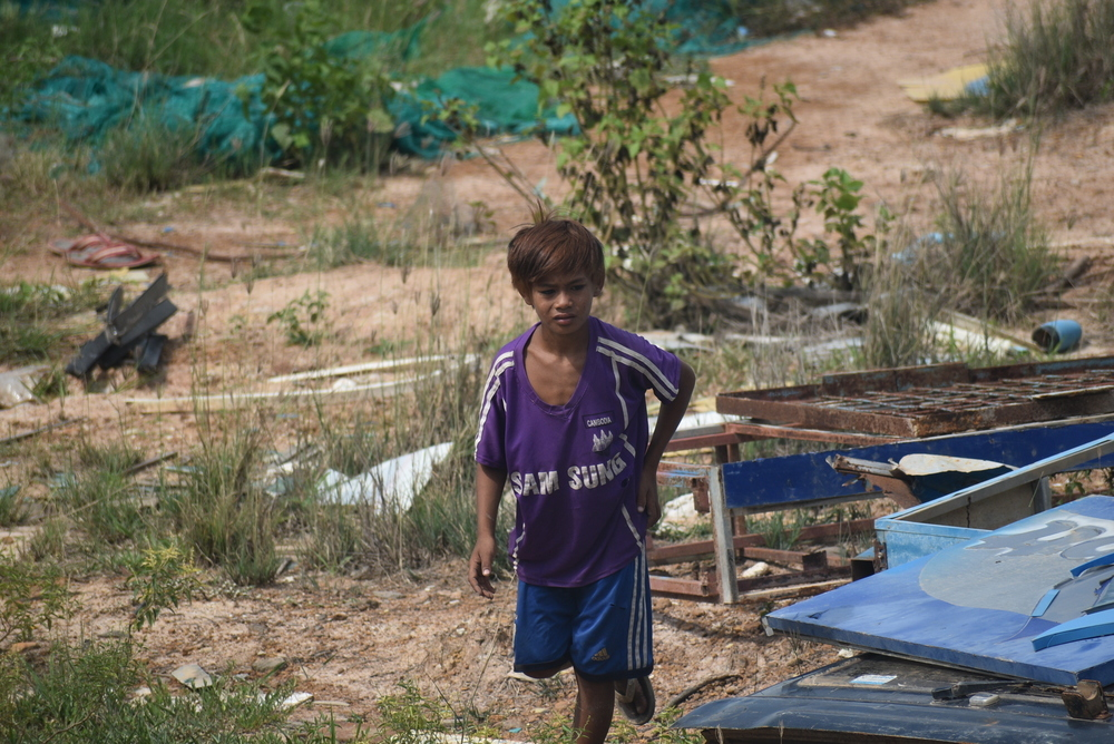 A Cambodian kid leading his band of kids, playing around the junkyard.